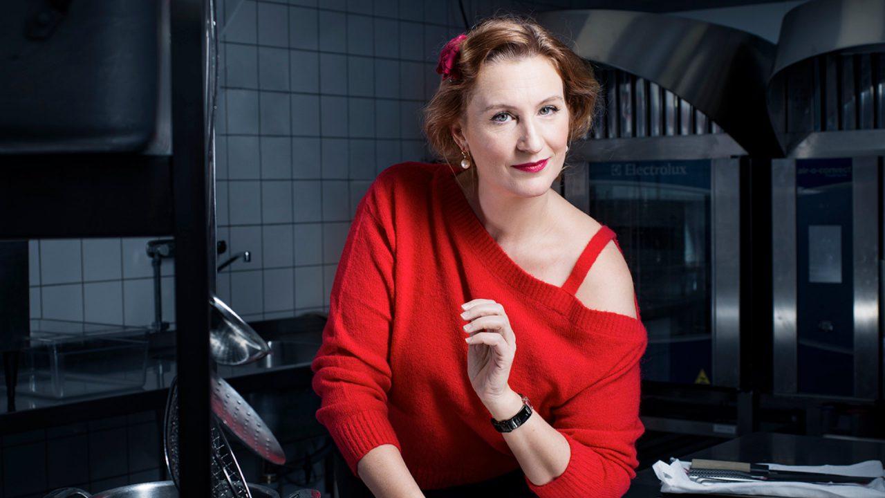 Kvinna i röd tröja som lutar sig fram mot barbänk